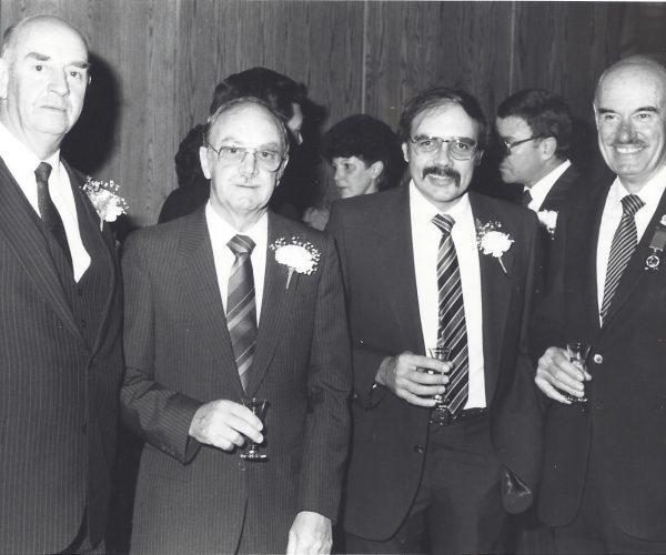 Foto met drie AHI presidente tydens die 1987 jaardinee van Pretoria Sakekamer geneem. Links is mnr Dries Niemandt. Tom Moodie staan tussen oud kollegas van Saambou Nasionale  Bouvereniging wat ook presidente van die AHI was. Christi Kuun links en Hendrik Sloet regs.